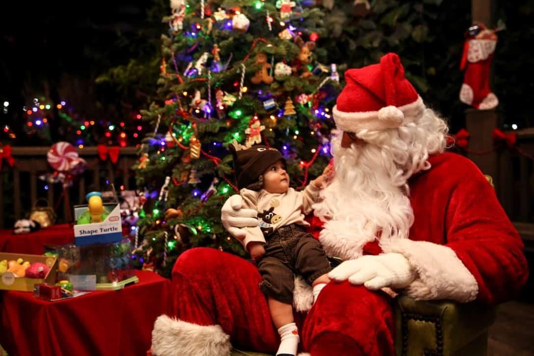 Pere Noël sous le sapin tenant un enfant dans ses bras