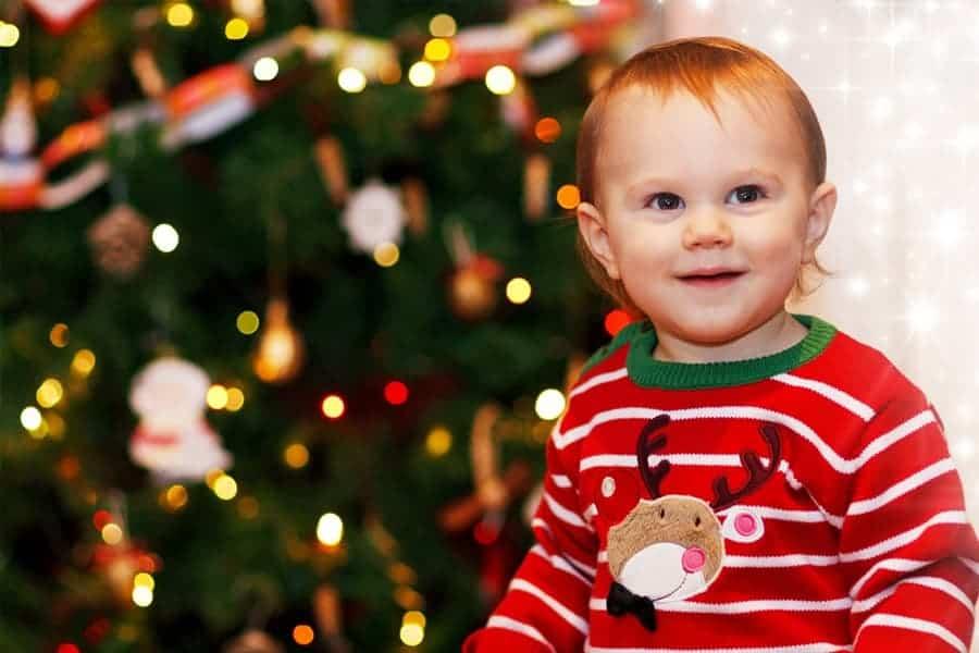 Bébé habillé avec un pull rayé rouge et vert