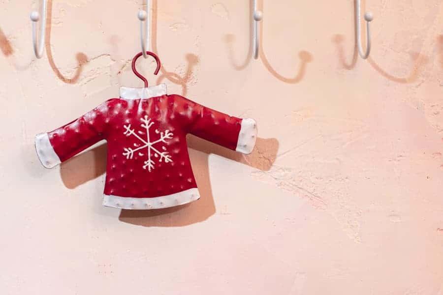 Sweat bicolore rouge et blanc accroché sur un cintre au porte-manteau