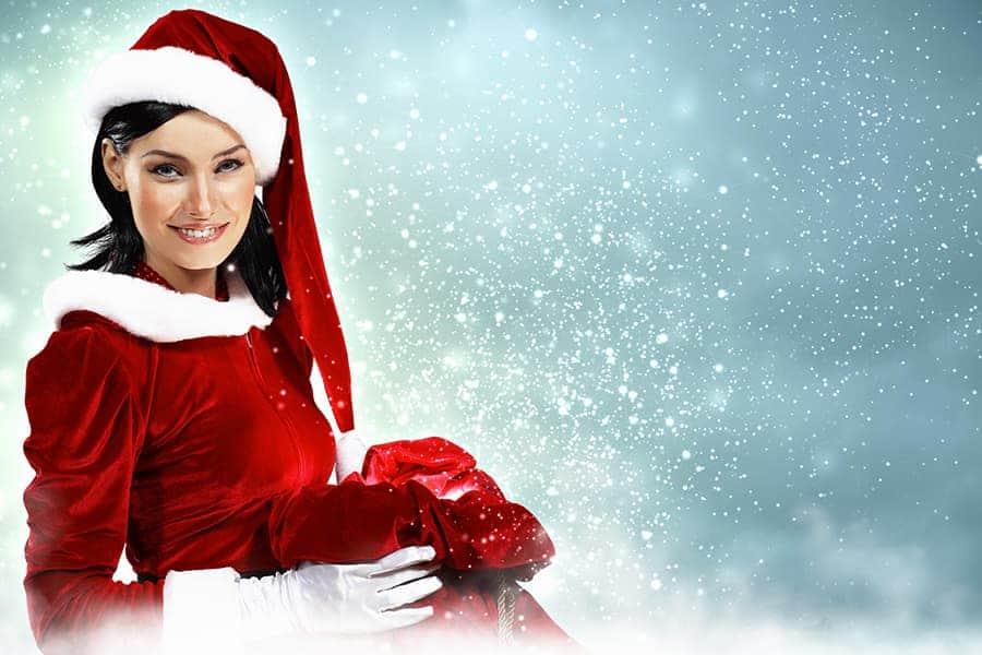 Femme portant un cadeau et une tenue de Noël avec un bonnet