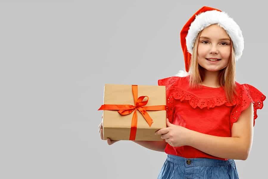 Enfant portant un cadeau et un bonnet pour Noël