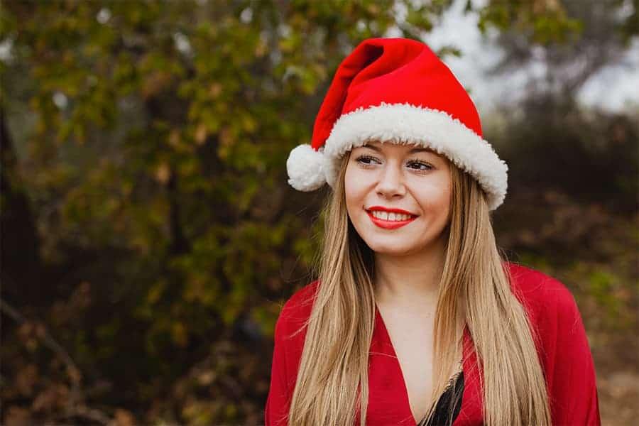 Femme dans la nature portant un bonnet de Noël rouge